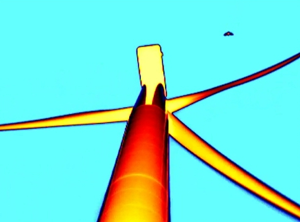 Thermal video still of bat approaching from downwind. The bat is black, the turbine is red-orange, and the sky is blue.