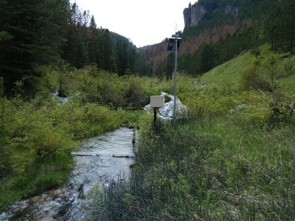 One of the types of sensors being used to capture the data. This photo shows a streamflow gage that measures water level or stage. Stage is then converted to discharge using a stage-discharge rating curve. On the pole is a solar panel that charges the battery. Above the panel is the transmitting antenna which communicates with the satellite to send data to the Internet in real time. The red trees on the hillside behind the gage are ponderosa pine trees recently killed by mountain pine beetles. If enough trees die, the water yield will increase streamflow at the gage.