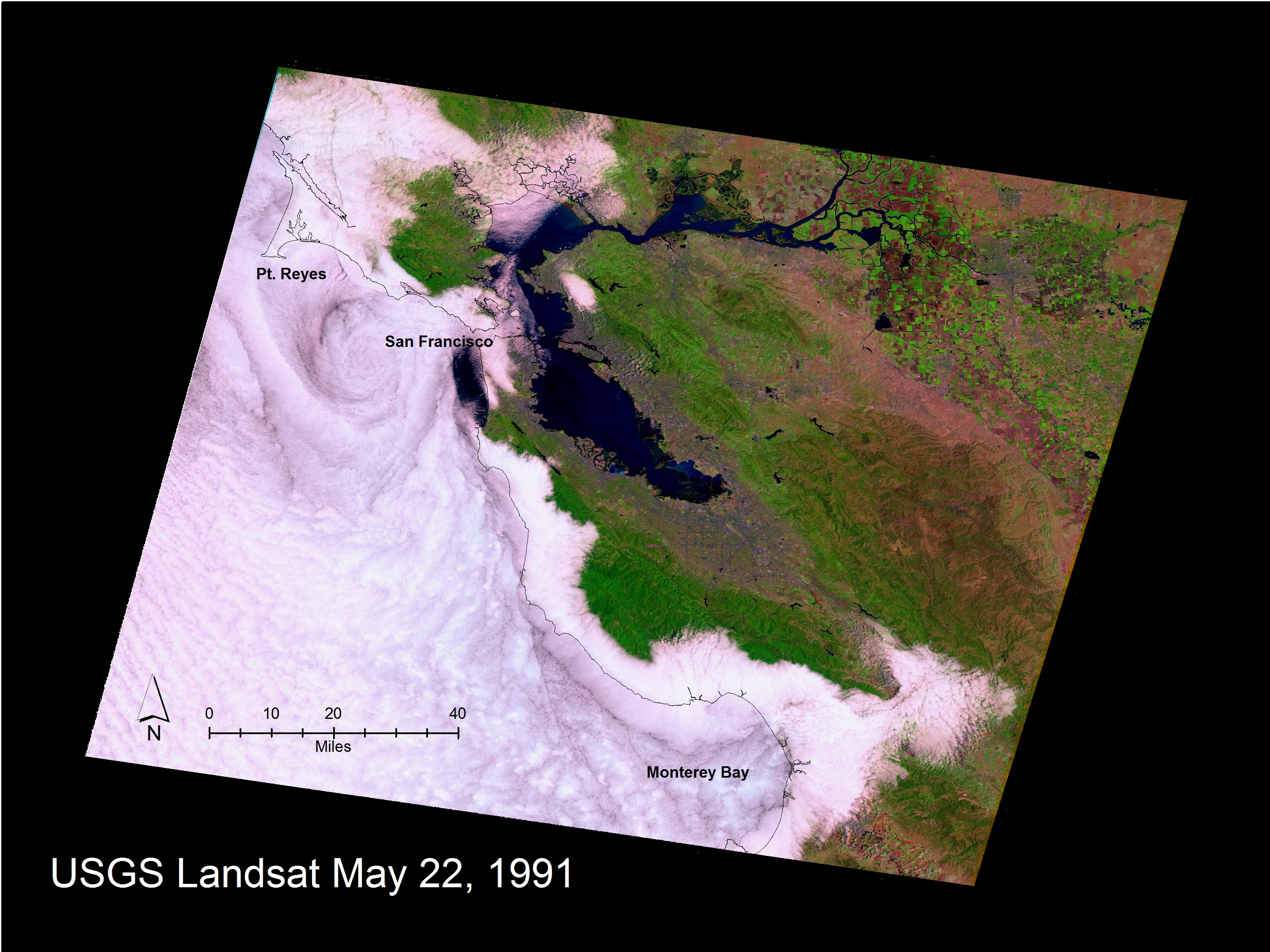 A Landsat image from May 22, 1991, shows the relative position of the coastline, mapped as a black line on top of the marine stratus and stratocumulus cloud layer along the San Francisco to Monterey, California, coastline. The effect of coastal mountains that form a topographic barrier keeping the marine layer offshore is visible, as are the gaps north of Point Reyes and to the east of Monterey Bay through which the clouds penetrate. A complex eddy pattern can be seen offshore of San Francisco in the lee of the Point Reyes peninsula that juts out to sea.