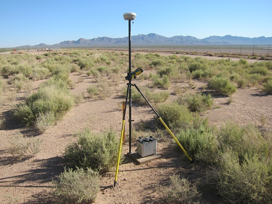 A GPS unit and a relative gravity meter are set up on a non-permanent relative gravity station adjacent to a Tucson Water recharge pond (located behind the fence in the background) near Tucson, Arizona. The source of the recharge is the Colorado River; water is moved through the Central Arizona Project aqueduct from Lake Havasu to the Phoenix and Tucson areas.