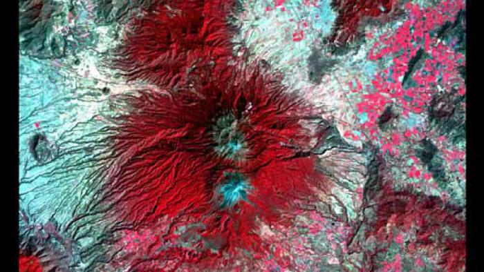 False color image of Colima Volcano. Two light blue peaks surrounded by red.