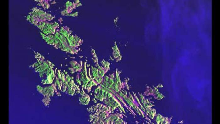Pink and green colored islands in the middle of deep blue waters.