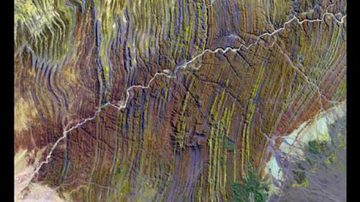 The Ugab River appears gray as it winds through wavy streaks of yellow, purple, and red.