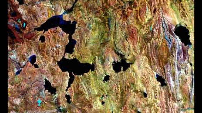 Colorful rough terrain with scattered black lakes.
