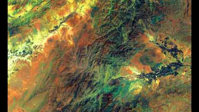Green and orange hue of rugged mountain terrain contains dashes of yellow.